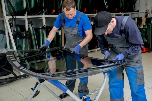 Trabalhadores especiais de automóveis substituindo pára-brisas de um carro na estação de serviço automóvel Foto Premium