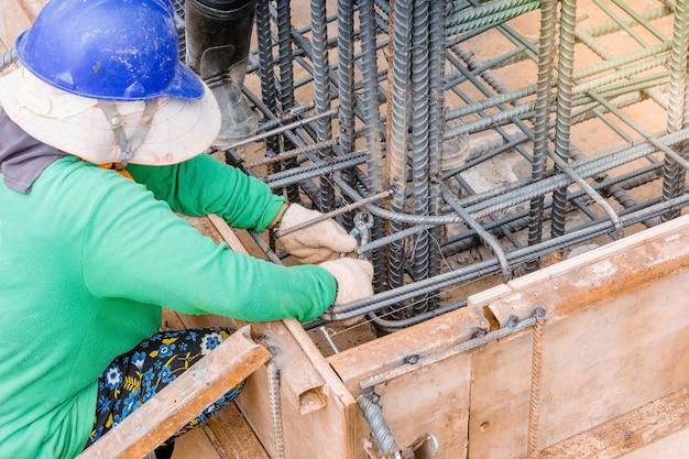 Trabalhadores mãos usando o fio de aço e pinças para garantir vergalhões Foto Premium