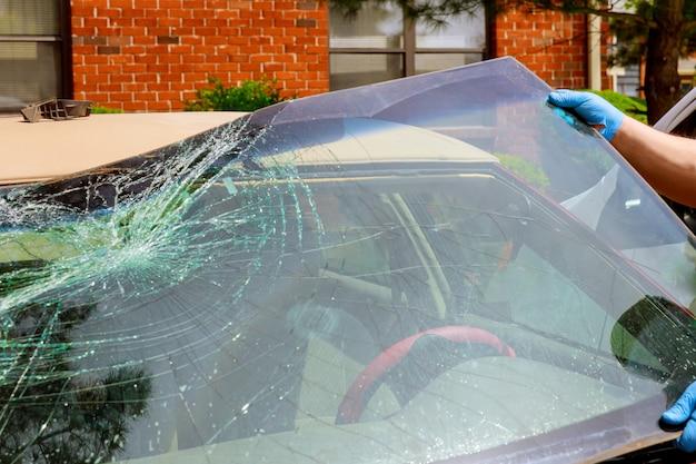 Trabalhadores removem pára-brisa quebrado de um carro em serviço automático Foto Premium
