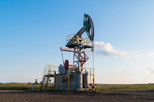 Trabalhando a bomba de óleo no chão entre os campos verdes Foto Premium