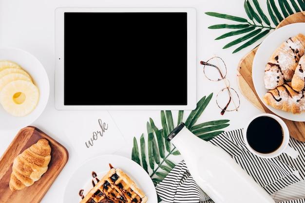 Trabalhar texto em papel perto do tablet digital; fatias de abacaxi; croissant; waffles; garrafa; xícara de café e óculos na mesa branca Foto gratuita