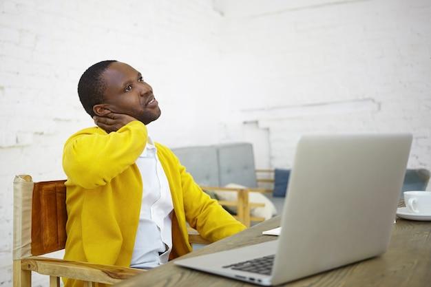 Trabalho, criatividade, ocupação e conceito freelance. retrato de um empresário próspero e elegante, de pele escura, sentado em frente a um laptop aberto na mesa, trabalhando no projeto inicial com olhar pensativo Foto gratuita