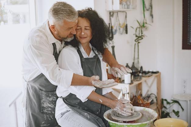 Trabalho criativo mútuo. casal adulto elegante com roupas casuais e aventais. pessoas criando uma tigela em uma roda de oleiro em um estúdio de argila. Foto gratuita