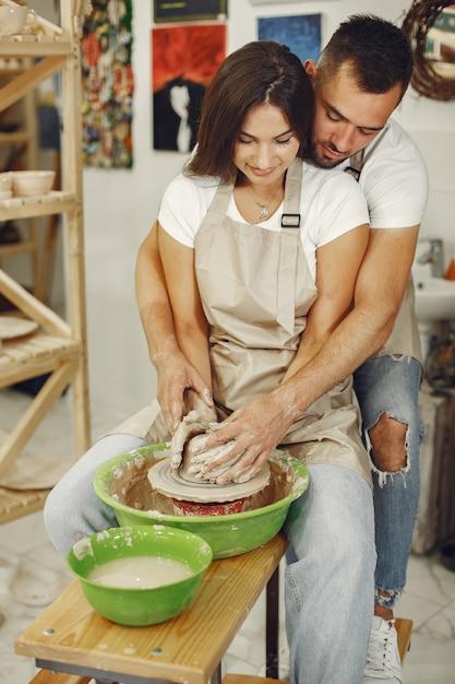 Trabalho criativo mútuo. jovem casal lindo em roupas casuais e aventais. pessoas criando uma tigela em uma roda de oleiro Foto gratuita