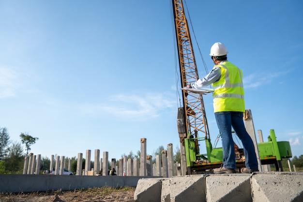 Trabalho de empilhamento de inspeção de engenheiro civil no local de construção de infra-estrutura Foto Premium
