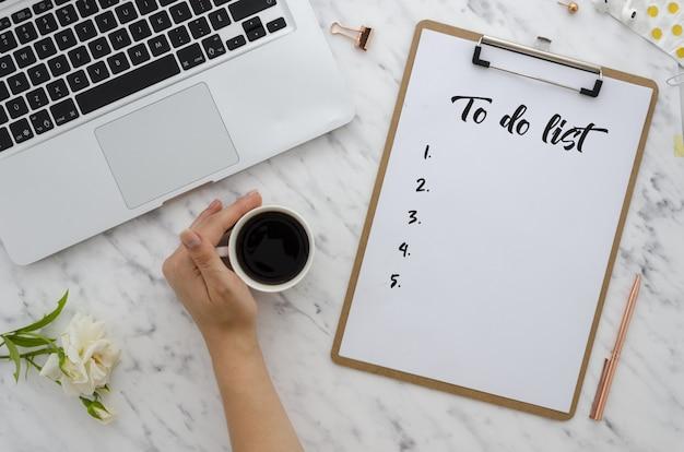 Trabalho de escritório plano leigos. menina que escreve a lista de tarefas na placa de grampo. computador, suprimentos, café Foto Premium