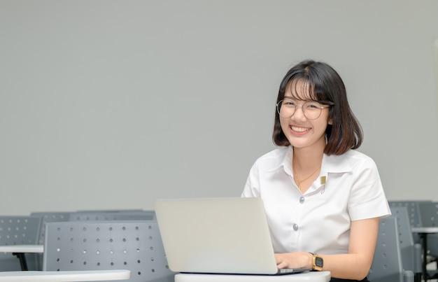 Trabalho de estudante bonito com laptop em sala de aula Foto Premium