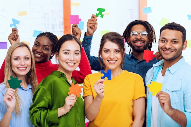 Trabalho em equipe de parceiros que trabalham juntos. conceito de integração e inicialização com peças de quebra-cabeça coloridas Foto Premium