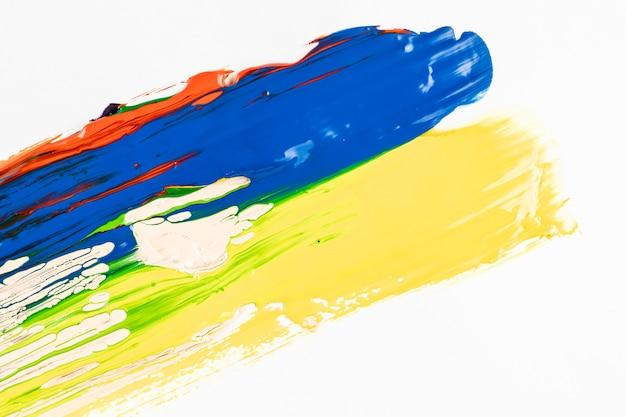 Traços de tinta azul e amarelo sobre fundo branco Foto gratuita