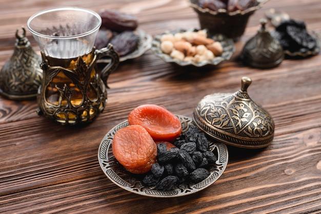 Tradicional chá turco e frutas secas na bandeja metálica sobre a mesa de madeira Foto gratuita