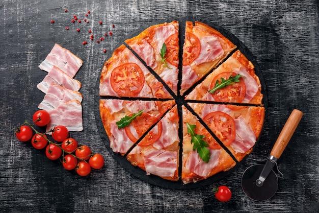 Tradicional pizza italiana com queijo mussarela, presunto, tomate, pimenta, especiarias pepperoni e rucola fresco Foto Premium