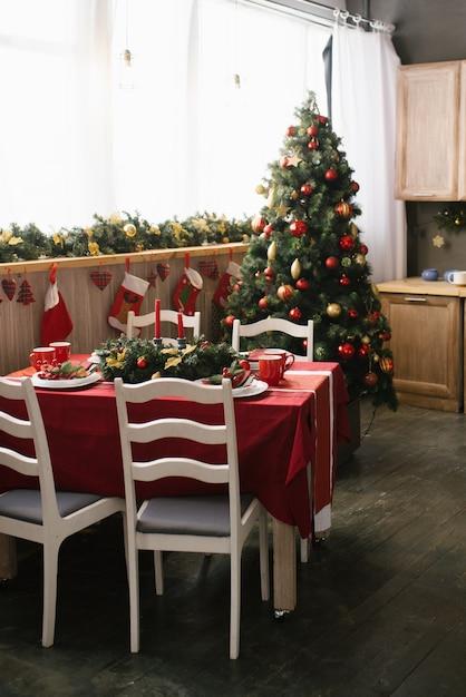 Tradicional sala de jantar decorada para o natal e ano novo, enfeitada com brinquedos, mesa e cadeiras de natal em vermelho e dourado. mesa de jantar Foto Premium