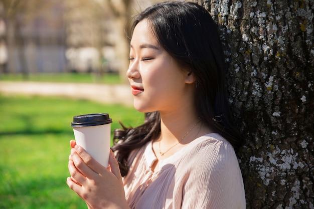 Tranquila garota tranquila desfrutando de café para viagem no parque da cidade Foto gratuita