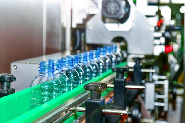 Transferência plástica clara das garrafas em automatização industrial automatizada dos sistemas de transporte para o pacote Foto Premium