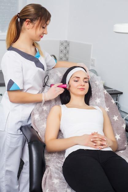 Tratamento facial rejuvenescedor. modelo recebendo massagem terapia de elevação em um salão de beleza spa. esfoliação, rejuvenescimento e hidratação. modelo e médico. cosmetologia. Foto Premium