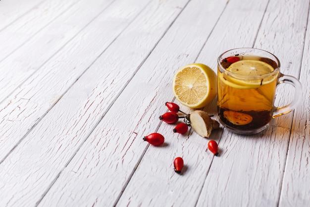 Tratar o frio. chá quente com limão e bagas fica na mesa de madeira branca Foto gratuita