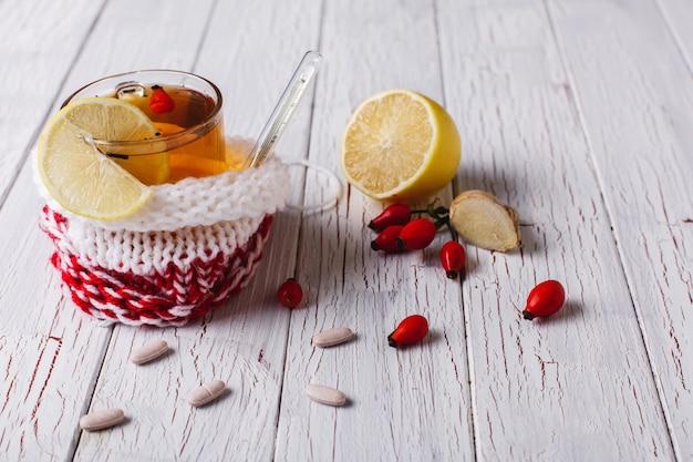 Tratar o frio. xícara com chá quente com limão e bagas fica em uma mesa Foto gratuita