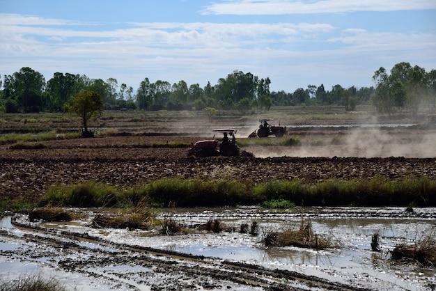 Trator está cultivando na paisagem da fazenda Foto Premium