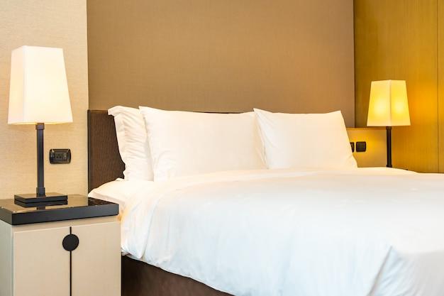 Travesseiro branco confortável e cobertor na cama com lâmpada de luz Foto gratuita