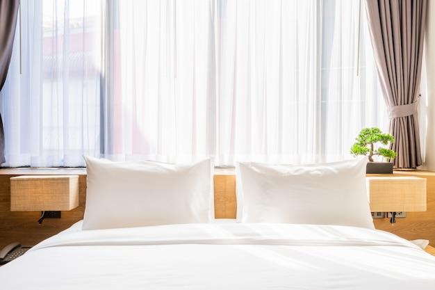 Travesseiro branco na cama decoração com luz da lâmpada e árvore verde em vasos no quarto de hotel Foto Premium