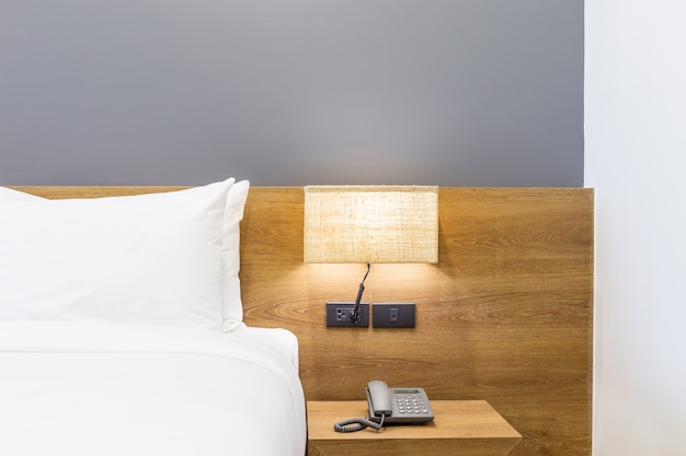 Travesseiro branco na cama decoração com luz da lâmpada e caixa de tecido no interior do quarto do hotel Foto Premium