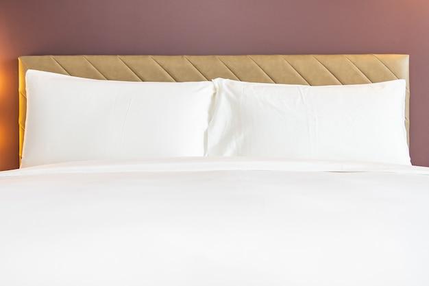Travesseiro confortável de cor branca e cobertor na cama Foto gratuita