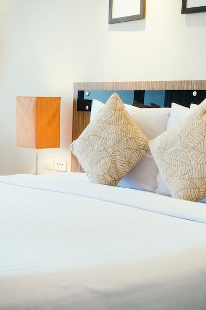 Travesseiro na cama com lâmpada de luz Foto gratuita