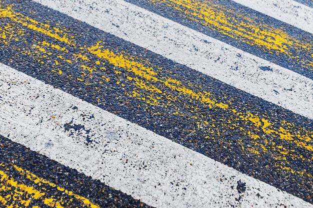 Travessia de pedestres, listras amarelas e brancas no asfalto molhado em forma de textura e substrato Foto Premium