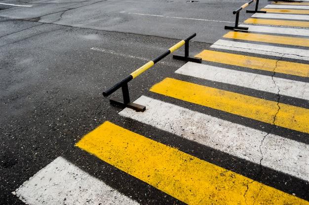 Travessia de pedestres perto dos estacionamentos, listras brancas e amarelas. Foto Premium