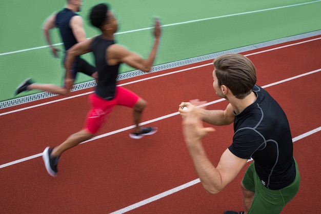Treinador bonito gritando perto de grupo jovem atleta multiétnico Foto gratuita