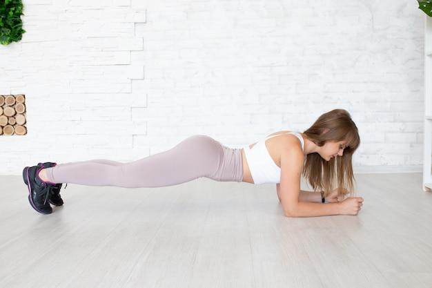 Treinador de fitness fazendo prancha para fortalecer seus bíceps, tríceps e abdominais. conceito de esporte feminino. Foto Premium