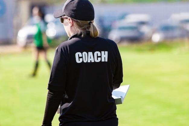 Treinador de futebol feminino na camisa preta de treinador em um campo de esporte ao ar livre, assistindo seu jogo de equipe Foto Premium
