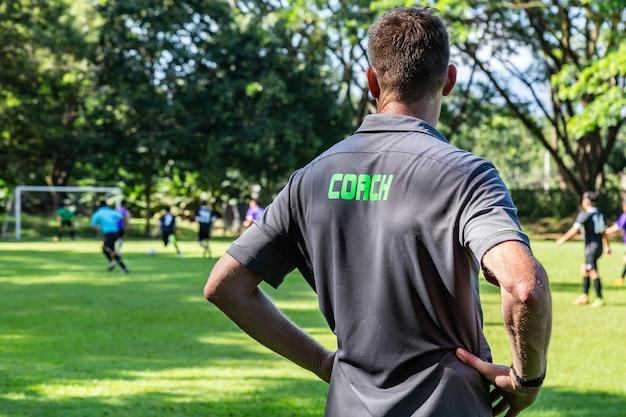 Treinador de futebol ou futebol masculino assistindo sua equipe jogar em um campo de futebol bonito Foto Premium