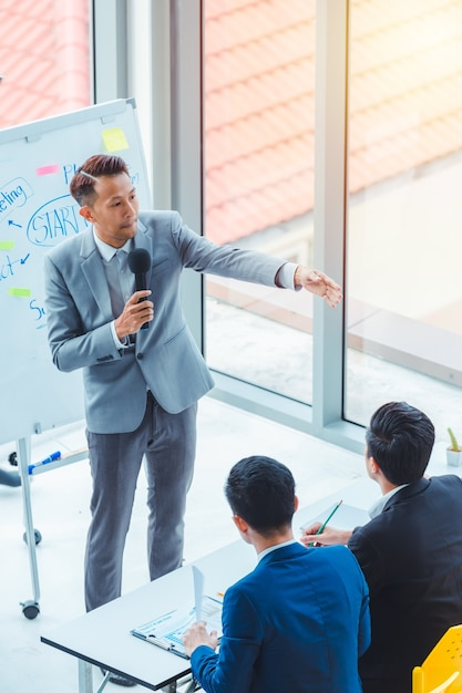 Treinador de homens de negócios asiáticos dando apresentação Foto Premium