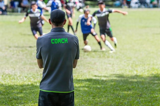 Treinador masculino do futebol ou de futebol que está na linha lateral que presta atenção a seu jogo da equipe Foto Premium