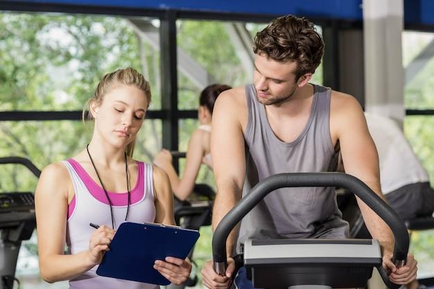 Treinador mulher falando com um homem a fazer bicicleta ergométrica no ginásio Foto Premium