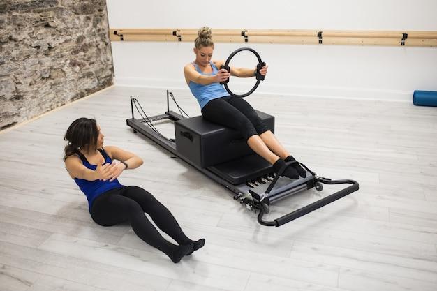 Treinadora ajudando mulher a se exercitar com anel de pilates Foto gratuita