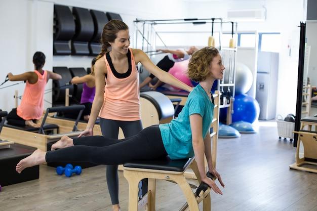 Treinadora ajudando mulher com exercícios de alongamento no reformador Foto Premium