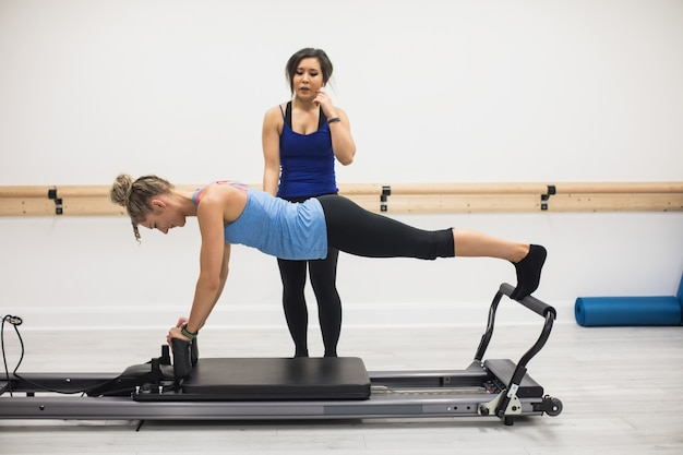 Treinadora ajudando mulher com exercícios de alongamento no reformador Foto gratuita