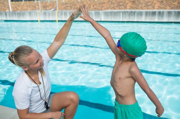 Treinadora treinando um menino para nadar Foto Premium