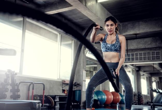 Treinamento apto do desportista asiático com corda da batalha no gym da aptidão. esporte e treino motivati Foto Premium