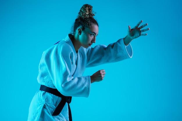 Treinamento ativo. judô feminino profissional no quimono de judô branco praticando e treinando isolado no fundo do estúdio azul neon. Foto gratuita