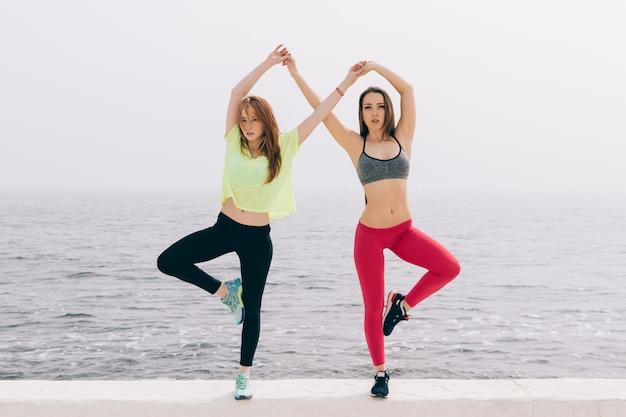Treinamento conjunto de duas meninas esportivas à beira-mar Foto Premium