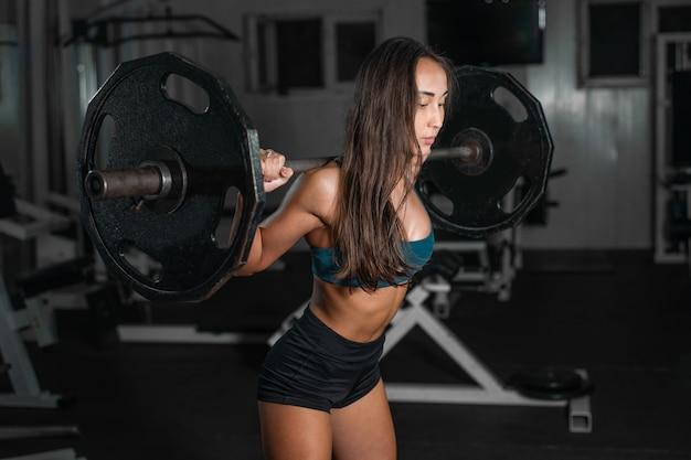 Treinamento feminino com barra, bombeando as pernas Foto Premium