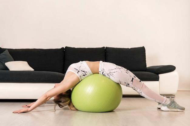 Treinamento feminino de alto ângulo com bola de fitness Foto gratuita