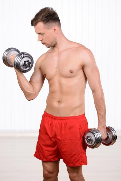 Treinamento muscular novo alegre do homem usando pesos. Foto Premium