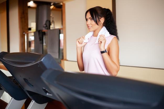 Treino cardio. caber as mulheres correndo em esteiras fazendo cardio-treinamento em uma academia, conceito de estilo de vida saudável Foto Premium