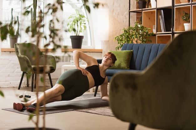 Treino com sofá. mulher jovem a fazer exercício em casa Foto gratuita