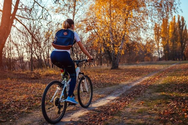 Treino de bicicleta no parque outono, motociclista jovem andando de bicicleta na floresta de outono, Foto Premium