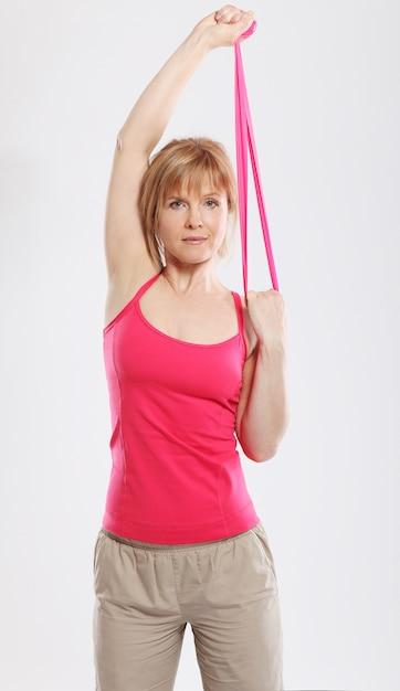 Treino desportivo e magro da mulher com fita rosa Foto gratuita